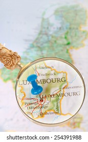 Blue tack on map of Benelux with magnifying glass looking in on Luxembourg, Europe
