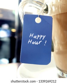 A blue tag hanging with a coffee cup , with text HAPPY HOUR.