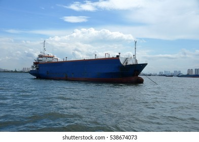The blue tanker ship at sea on a background of blue sky and city of Jakarta