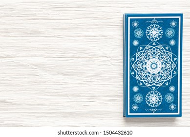 Blue tarot cards deck on white wooden table background with a copy space.