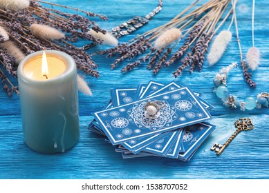 Blue tarot cards deck on blue wooden table background.