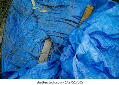 Blue tarp background with chicken wire and old boards for construction DIY home renovation poultry coop.