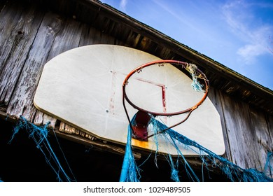 A blue tarp hanging from an abandoned and collapsing barn/garage.