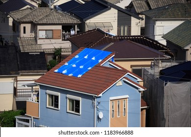 Blue tarp on roof in Japanese neighborhood after damage from typhoon