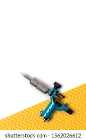 Blue tattoo machine on creative white and yellow background. Tattooing artist studio minimal layout with copy space