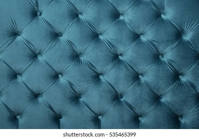 Blue teal velvet capitone textile background, retro Chesterfield style checkered soft tufted turquoise fabric furniture diamond pattern decoration with buttons, close up