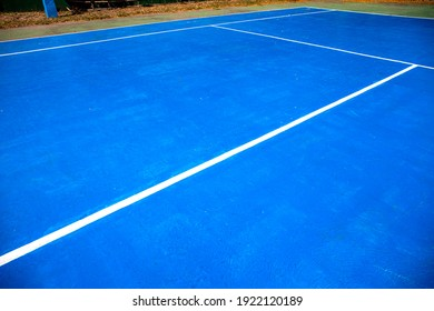 Blue tennis court abstraction. Empty sport field photo. Hard court cover for lawn tennis. Summer sport activity outdoor. White markup on blue court. Sunny day on tennis court. Sport field in park