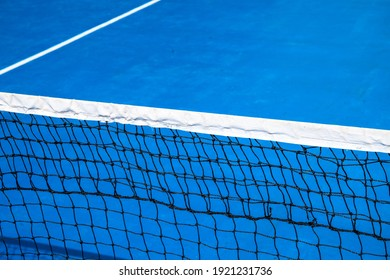 Blue tennis court with net. Empty sport field photo. Hard court for lawn tennis. Summer sport activity game outdoor. White markup on blue court. Sunny day on tennis court. Sport field in park