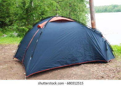 Blue tent in forest, camping. Tourism, lifestyle, activity