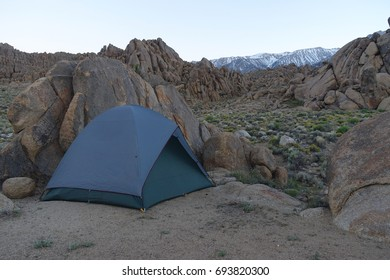 A blue tent set up against rocks in the evening at Alabama Hills in Lone Pine, California