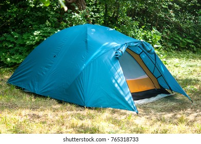 The blue tent stands on the edge of the forest.