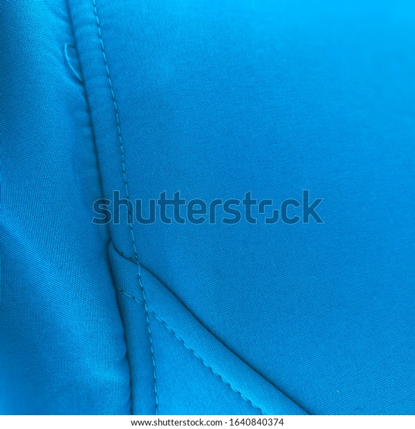 Blue textile close up. Azure seam aligned vertically. Negative space on the right side