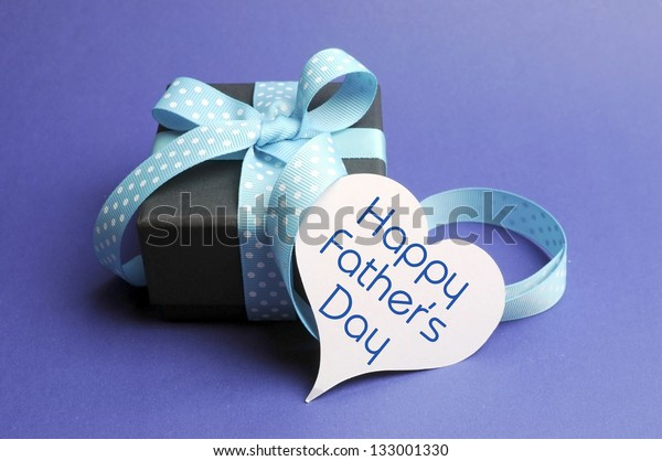 Blue theme black box present gift with polka dot ribbon and white heart shape tag with Happy Fathers Day message