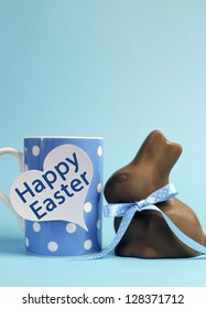 Blue theme polka dot breakfast coffee mug with chocolate bunny rabbit and heart shape message saying Happy Easter. Vertical with copy space for your text here