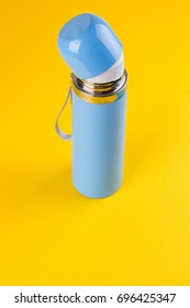 Blue thermos for hot drinks on a yellow background