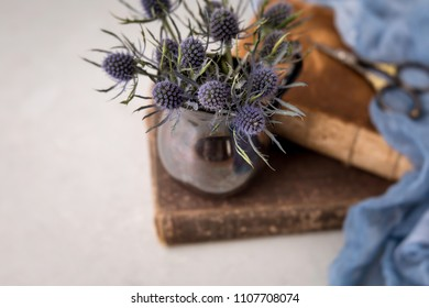 Blue Thistle Flower Still Life; Thistle in Tarnished Silver Creamer on Antique Books