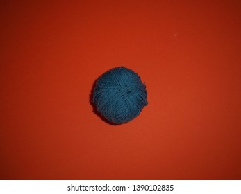 Blue threads on an orange background.  Skein thread.  Skein of blue threads on an orange background