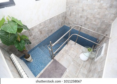 Blue tiled Mikveh, or ritual bath, with railing and steps, is used by Jews for purification, immersion, and spiritual cleansing
