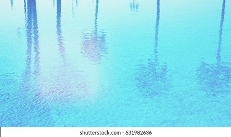 blue tiled pool with  reflections of palm trees , retro toned