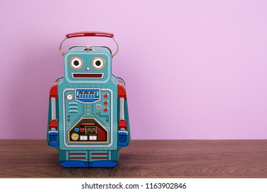Blue tin box robot on wooden floor and purple background