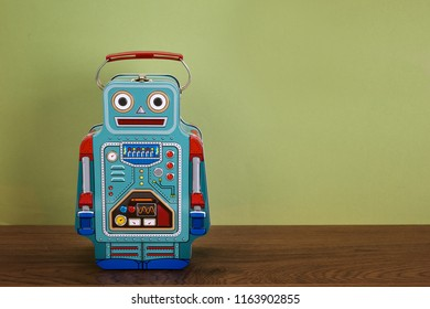 Blue tin box robot on wooden floor and green background