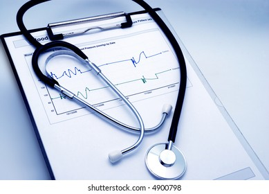Blue tint Stethoscope on clipboard over blood pressure graph printout