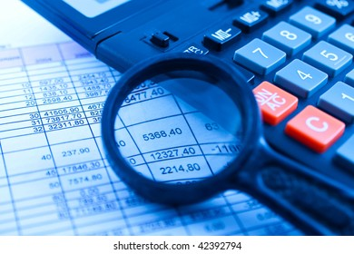 blue tinted image of selective focus shot of calculator magnifying glass on financial pages of broadsheet