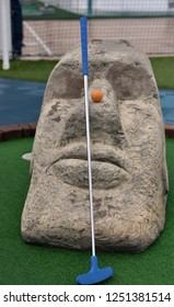 Blue tipped Minigolf putt and orange ball is resting on the nose of an easter island head in an authentic minigolf parka