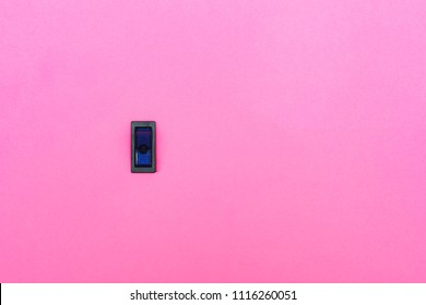 Blue toggle switch on a pink background. Abstract photo with blank empty space for free title