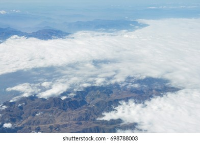 Blue tone Sea of clouds and mountain scene from plane window