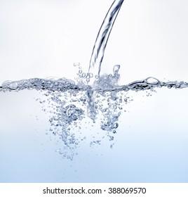 Blue tone water splashing against white background.