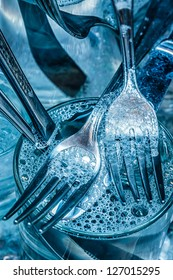 Blue toned cutlery and glasses being washed with water and detergent