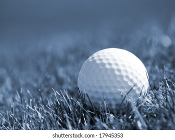 Blue toned image of golf ball in grass