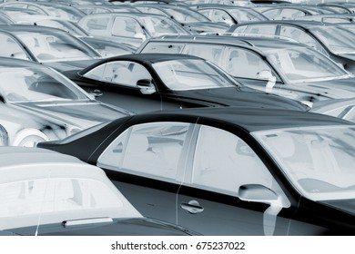 Blue toned, negative image of rows of parked cars.