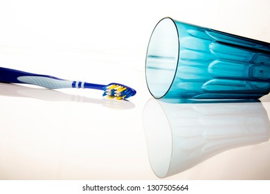 Blue toothbrush and glass on white background.