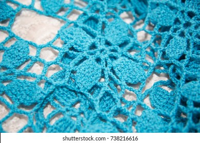 Blue top knitted in manual photographed in close-up. The product is handmade.