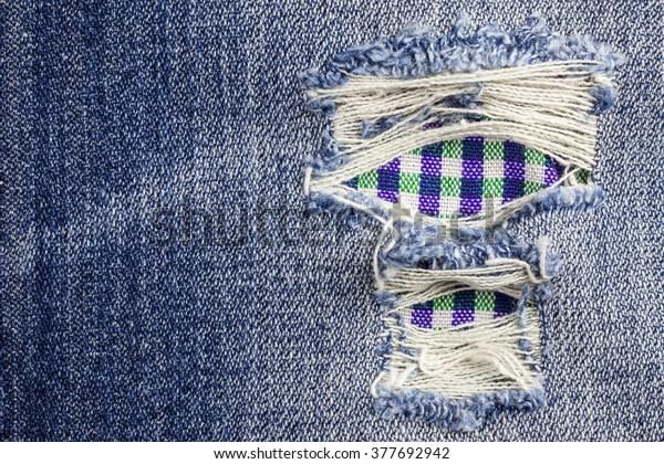 Blue torn denim jeans texture background.
