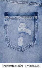 Blue torn jeans . Detail of vintage blue jeans texture with pocket.Pocket on jeans denim fashion background .