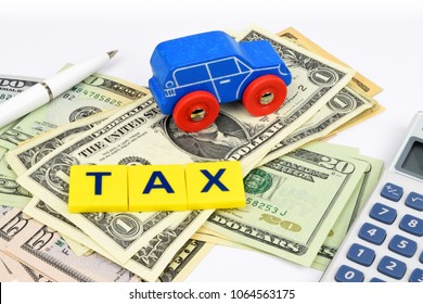 A blue toy car, pen, calculator and the word TAX, sits on a bed of Dollar currency notes. A financial still life on the subject of motoring cost.