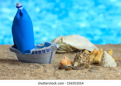 Blue toy ship on sand, on blue background