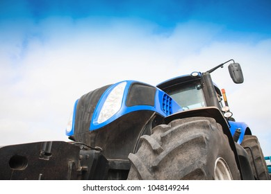 Blue tractor close-up against the sky