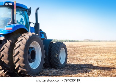 Blue tractor on the background of an empty field and a clear blue sky