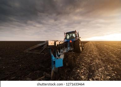 Blue tractor Plowing in dusk