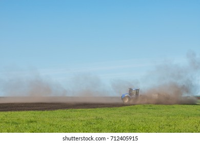 blue tractor plowing the field