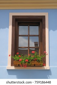 Blue traditional romanian house with a wooden window in a white frame on a sunny summer day. Red flowers in a jardiniere.