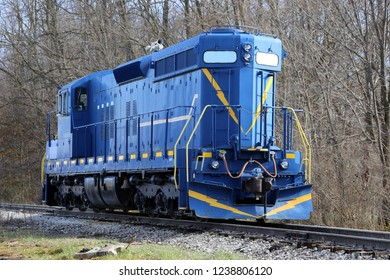A blue train engine sitting on the railroad tracks by itself