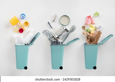 Blue trash bins and assorted garbage on grey background. Recycle concept