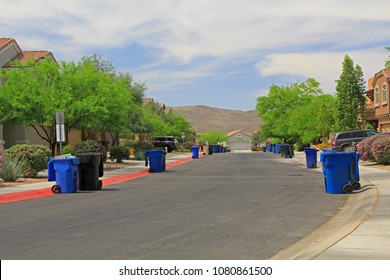 Blue trash cans line the street on trash day in a Tucson Neighborhood with blue sky copy space.