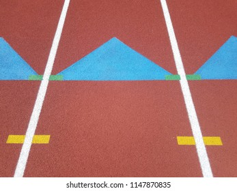 blue triangles, white lines, and orange running track surface