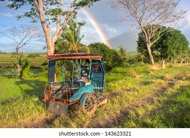 A blue tricycle taxi parked on a dirt road next to a rice field at the base of Mount Isarog in Caramines Sur province, Philippines.